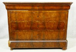 A 19th century French Louis Phillipe figured mahogany commode with marble top above four long