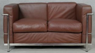 After Le Corbusier, an LC2 Cassina two seater sofa in piped leather upholstery on tubular chromium