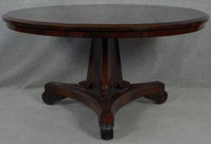 A Regency rosewood tilt top dining table on acanthus scroll carved pedestal and platform base. H.