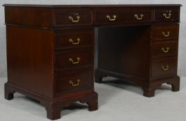 A Georgian style mahogany three section pedestal desk with an arrangement of nine drawers on bracket