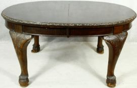 An early 20th century mahogany Georgian style dining table with extra leaf and wind out mechanism on