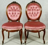A pair of 19th century carved mahogany side chairs in deep buttoned upholstery on cabriole supports.