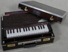 A modern portable harmonium from the Calcutta Harmonium Shop in metal bound hardwood carrying