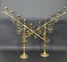 A large pair 19th century brass menorahs of angular form raised on turned scrolling foliate bases.