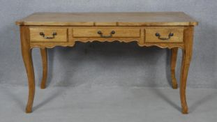 A French Provincial fruitwood Louis XV style bureau plat with three frieze drawers raised on slender