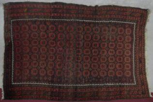 An Eastern rug with repeating star motifs across the madder ground contained by stylised geometric