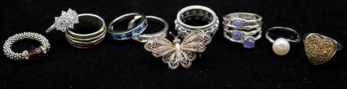 A collection of nine rings and a silver butterfly filigree brooch. Including two Swarovski and