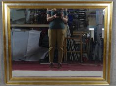 A bevelled wall mirror in gilt and silvered frame. H.90.5 W.116cm