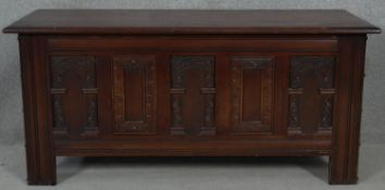 A mid century oak 18th century style coffer with carved panels on block supports. H.52 L.114 W.45cm