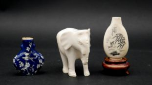 An antique Japanese ivory snuff bottle on wooden stand with engraved koi carp and water weed