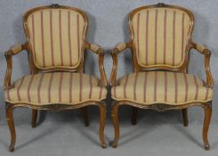 A pair of French provincial style carved walnut open armchairs on cabriole supports. H.84cm