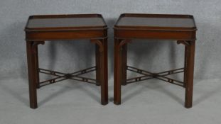 A pair of Georgian style mahogany lamp or bedside tables on chamfered square section pierced