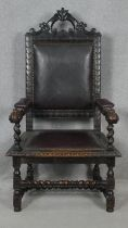 A late 19th century oak throne armchair in the Carolean style with carved cresting and arms in