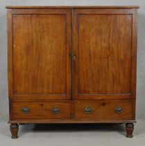 An early 19th century mahogany linen press with panel doors enclosing linen slides above a pair of