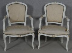 A pair of white painted and gilt French style open armchairs on cabriole supports. H.88cm (some