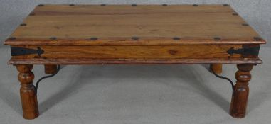 An Indian teak metal bound coffee table on circular section supports. H.40.5 L.110.5 W.61cm
