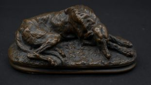 A bronze figure of a resting greyhound on a naturalistic base. L.15cm