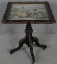 A Victorian carved and painted tilt top table with acorn and oak leaf detail and glazed inset