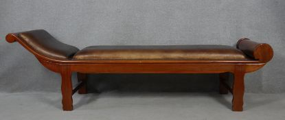 An Eastern teak framed chaise longue in studded leather upholstery. H.66 L.222 W.68cm