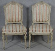 A pair of carved and painted Louis XVI style side chairs in striped damask upholstery. H.99cm