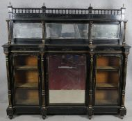A late Victorian ebonised mirror backed credenza with allover incised gilt carving the bevelled