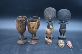 A pair of carved Ashanti fertility figures, a set of four carved goblets and other carved items. H.