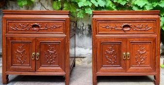 A pair of Chinese hardwood bedside cabinets with floral carved doors and drawers on shaped block