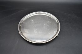 A silver card tray with gadrooned edge on triple supports, engraved, hallmarked Birmingham 1931.