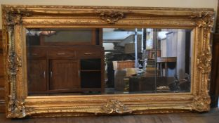 A large bevelled glass wall mirror in heavy gilt Rococo style frame. H.99 W.190cm