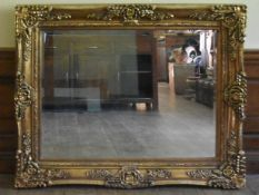 A bevelled glass wall mirror in heavy Rococo style frame. H.103 W.130cm