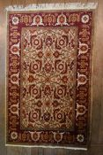 A Ziegler style rug with serrated palm and lotus decoration on a fawn ground within a