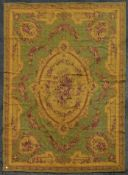 A handmade needlepoint carpet with central medallion with swags and bouquets on a sage ground within