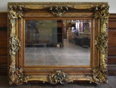 A bevelled glass wall mirror in heavy Rococo style frame. H.89 W.114cm