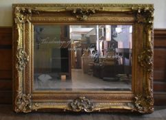 A gilt framed wall mirror in a heavy Rococo style frame, the bevelled plate with Oscar Wilde