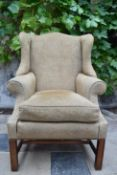A Georgian style wingback armchair on square stretchered supports. H.109 W.82 D.84cm