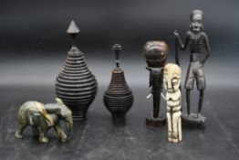 A carved bone figure, two turned African hardwood lidded pots, a carved stone elephant and other