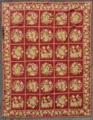 A hand made needlepoint carpet with repeating floral sprays across the brick red field contained