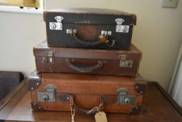 A small leather case fitted with filing drawers, a vintage leather suitcase and another vintage