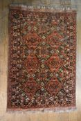 A Shirvan rug with repeating floral lozenge medallions on a madder ground within flowerhead borders.