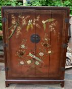 A lacquered Japanese cabinet with bi-fold doors and all over painted exotic bird and blossom