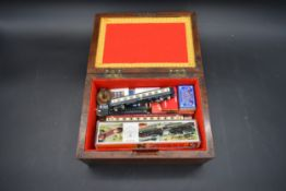 A 19th century mahogany box containing boxed Minitrix model railway carriages etc. H.13 W.26 D.