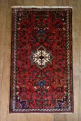 A Persian rug with central star medallion on a burgundy ground decorated with stylised foliate