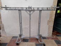 An unusual folding and mobile metal framed coat hanging rack on casters. H.160 W.35cm (closed)