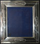 A large Italian silver easel picture frame with knotted cord and hammered decoration, marked