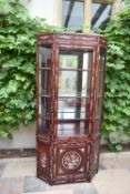 A Chinese hardwood two section floor standing display cabinet with profuse all over mother of