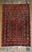 An Eastern prayer rug with repeating gul motifs on burgundy ground with stylised floral multi