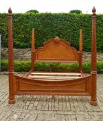 A large American Colonial style elm four poster bedstead with fluted column and spiral finials, to