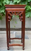 A Chinese carved hardwood urn stand with pierced frieze on shaped square stretchered supports. H.
