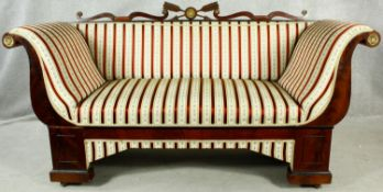 A 19th century Continental mahogany and ebonised framed sofa with carved back rail and ormolu