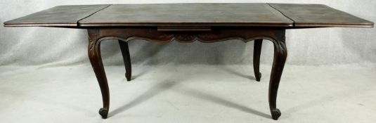 A C.1900 French oak draw leaf extending dining table with parquetry inlaid top raised on carved